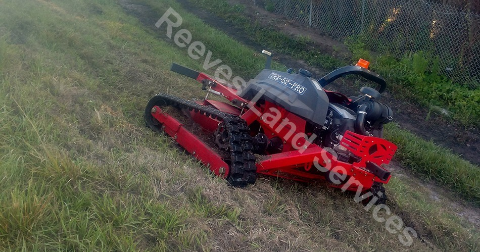 Remote control mower on hillside slope.